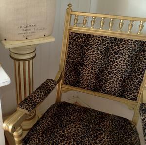Gammal fåtölj i kitchigt guld och leopard