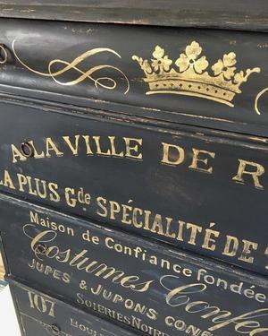 Svart stor byrå med fransk guldtext