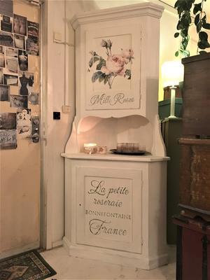 Hörnskåp med rosor och fransk text