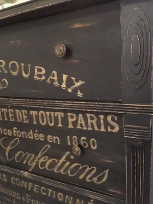 Antik svart byrå med vackra detaljer och fransk text i guld