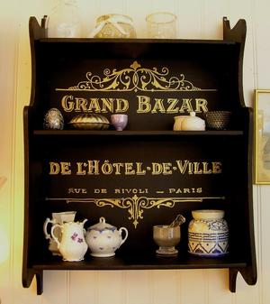 Svart hylla med guldtext Grand Bazar